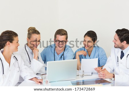 Happy medical team discussing over laptop in hospital