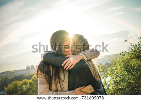 Happy meeting of two friends hugging at sunset outdoor - Pleasant moment of young sisters embracing in the wilderness as the sun shines upon them - Vignette editing