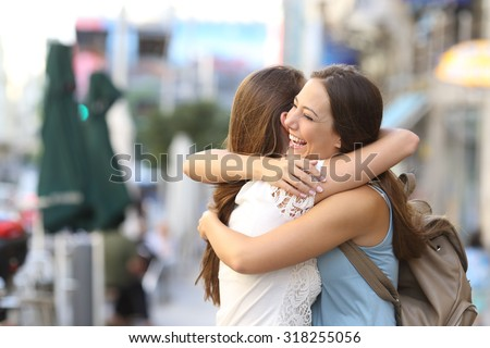 Shutterstock Happy meeting of two friends hugging in the street