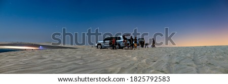 Happy men and a woman in two sport utility vehicles (SUV) in Qatar desert (Inland sea) ,  on a full moon night, enjoying view of stars in the sky. Night, long exposure panorama.