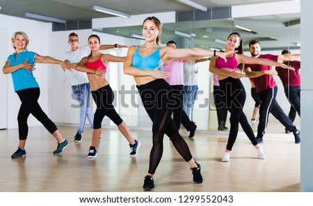 happy men and ladies dancing aerobics at lesson in the dance class