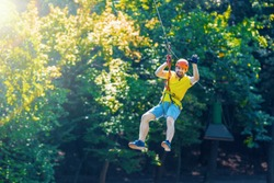 Happy men boy male gliding climbing down in extreme road trolley zipline in forest on carabiner safety link on tree to tree top rope adventure park. Family weekend children kids activities concept