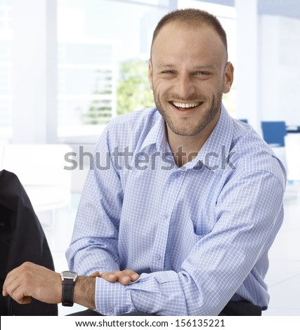 Happy mid-adult businessman sitting at office, laughing.