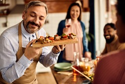 Happy mid adult man serving healthy bruschetta while having a meal with friends at home.