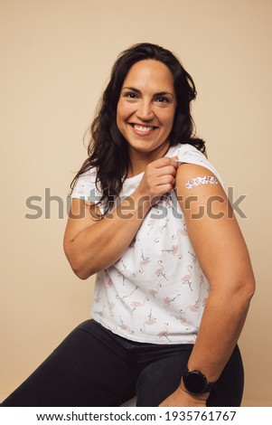 Happy mid adult woman showing a bandage on her arm after she received vaccination. Woman feeling proud to get inoculated.