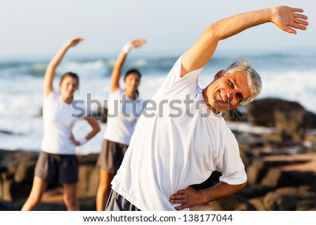 happy mid age man exercising at the beach with his family