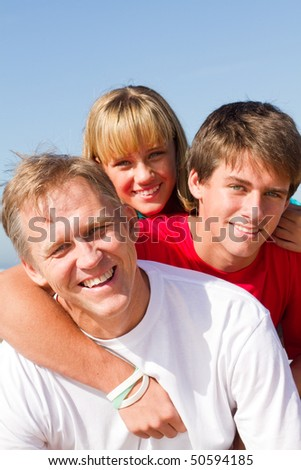 happy mid-aged father and children on beach