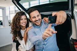Happy middle age couple enjoying while choosing and buying new car at showroom. They making selfie photo with their new car.