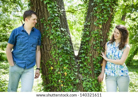 Happy middle-age couple standing next to v shaped tree in park