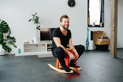 Happy middle aged bearded man, riding toy children's moose at home. In a spacy bright apartment, with few furniture.