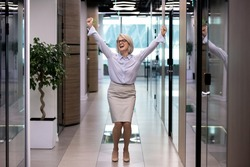 Happy middle-aged business lady celebrates personal business goal achievements standing dancing in corridor office hallway raised hands scream with joy feels excited. Growth progress in career concept