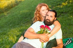 Happy middle-aged couple in love on a background of green nature. The man gave the woman a bouquet of roses.