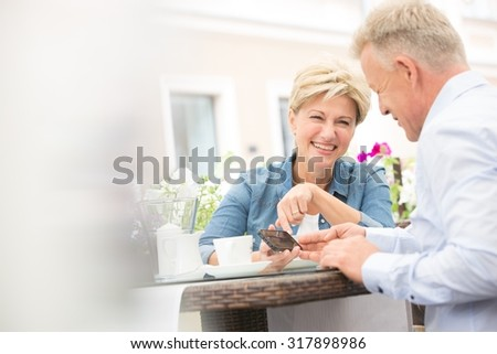 Happy middle-aged couple using mobile phone at sidewalk cafe