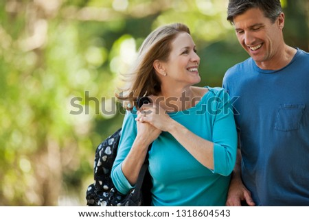 Happy middle aged couple walking in the park. #1318604543