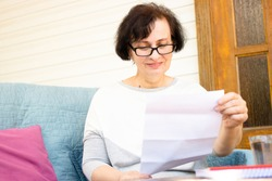 Happy middle aged elderly woman in eyeglasses reading paper document or postal letter from friend, sitting on sofa on home terrace. Rejection of pleasant paperwork bank notice or post correspondence