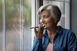 Happy middle aged elderly woman recording audio message or using voicemail mobile function, standing near window. Smiling 60s old lady activating virtual assistance or web surfing information online.