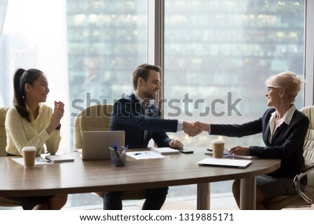 Happy middle aged executive businesswoman handshaking new male partner at diverse team meeting, mature female ceo shake hands rewarding employee celebrate successful deal welcoming for collaboration
