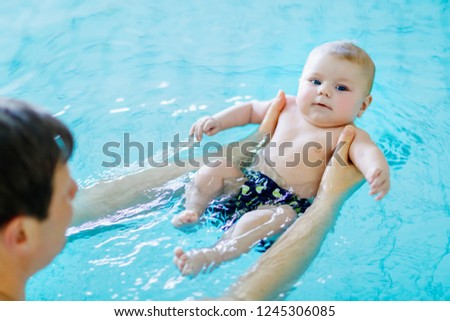 Happy middle-aged father swimming with cute adorable baby in swimming pool. Smiling dad and little child, newborn girl having fun together. Active family spending leisure and time in spa hotel.