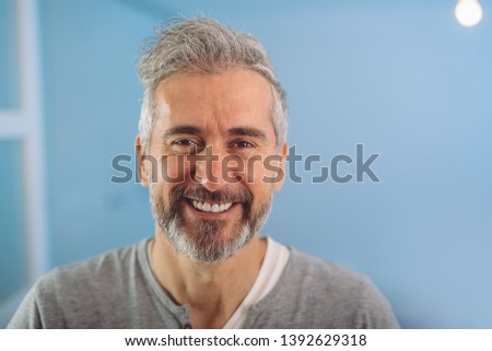 happy middle aged gray haired bearded man smiling