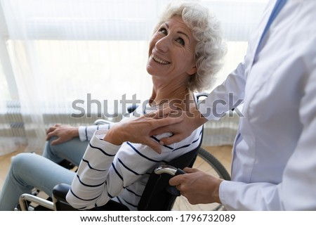 Happy middle aged handicapped woman sitting in wheelchair, looking at medical worker. Smiling disabled retired female older patient feeling thankful to physiotherapist, rehabilitation recovery concept