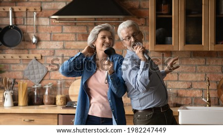 Happy middle-aged hoary wife and husband dancing in kitchen listen music singing song using kitchenware like microphones enjoy karaoke together feel carefree. Hobby, untroubled retired life concept Photo stock ©