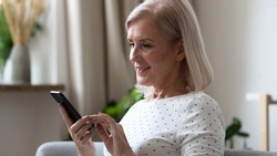 Happy middle aged lady holding smartphone, sitting on sofa at home. Smiling elderly woman searching information, typing message in social networks, using mobile applications, head shot close up.