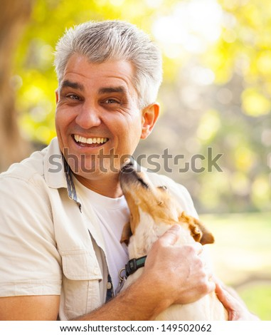 happy middle aged man and pet dog outdoors