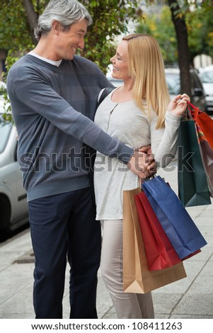Happy middle aged man embracing woman on sidewalk while carrying shopping bags