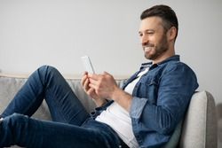 Happy middle-aged man in casual resting on couch at home, using modern smartphone, copy space. Handsome bearded man reading blog or playing games on newest mobile phone, having fun on weekend