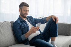 Happy middle-aged man in casual sitting on couch at home, using mobile phone, copy space. Handsome bearded man reading blog or playing games on newest smartphone, having fun on weekend