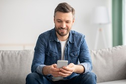 Happy middle-aged man in casual sitting on couch at home, using modern smartphone, copy space. Handsome bearded man reading blog or playing games on newest mobile phone, having fun on weekend