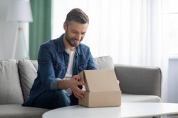 Happy middle-aged man unpacking delivery box, sitting on couch by tea table, home interior. Satisfied customer cheerful man opening package, ordering clothes or gadgets on Internet, copy space