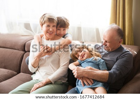 Happy middle-aged mature grandma and drandpa with  little preschooler two grandsons having fun playing at home.