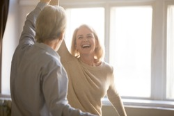 Happy middle aged mature woman enjoying dancing with elder husband at home, active healthy senior old couple man and woman pensioners having fun in waltz laughing bonding celebrating anniversary
