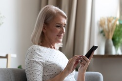Happy middle aged mature woman enjoying using mobile apps texting typing messages sit on sofa, smiling old adult lady holding smartphone looking at cellphone screen browsing social media at home