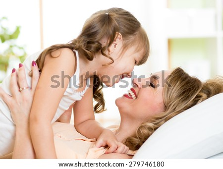Happy middle-aged mom playing with her kid daughter in bed enjoying  sunny morning in home bedroom