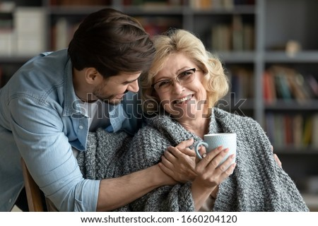 Happy middle-aged mother relax in chair drink tea enjoy family weekend reunion with grown-up son, smiling senior 70s mom rest at home spend time with caring adult man child, bonding concept