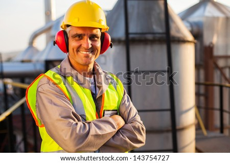 happy middle aged oil chemical industry worker inside plant