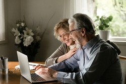 Happy middle aged pensioner mature family couple have fun using online app on laptop at home. OAP retired wife and elderly husband watch or read funny content on computer, typing, hugging and laughing