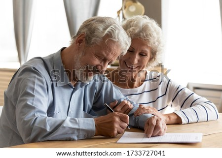 Happy middle aged retired couple signing marriage contract, feeling excited of right decision. Smiling family spouses putting signature after making testate in office or agreement with professional. Foto stock ©