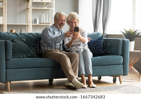 Happy middle-aged 50s husband and wife sit rest on couch in living room have fun making self-portrait picture on cell, excited elderly 60s couple laugh taking selfies using modern smartphone together