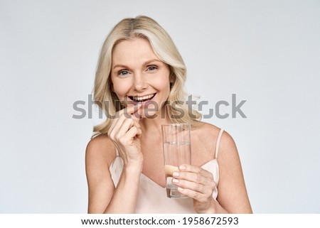Happy middle aged 50s woman holding pill and glass of water taking dietary supplements. Portrait of smiling adult attractive woman taking care of health in menopause, isolated on white. Сток-фото ©