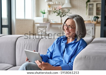 Happy middle aged senior woman sitting on couch holding using digital tablet device during video call with family friends. Older female reading ebook or watching zoom video meeting online.