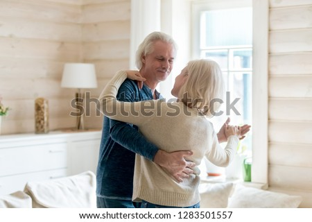 Happy middle aged spouses in casual clothes celebrating long lasting living together anniversary standing in cozy light living room, loving grey haired husband embracing beloved wife and dancing tango