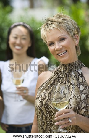 Happy middle aged woman holding wine glass with female friend
