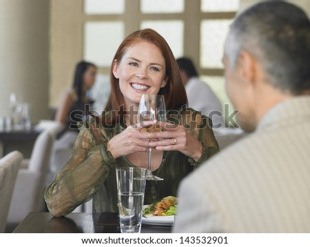 Happy middle aged woman smiling at man over meal in restaurant