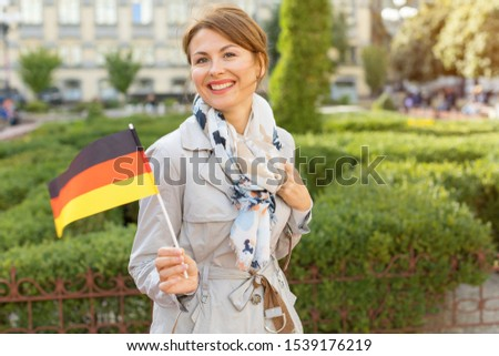 Happy middle aged woman with the German flag on a background of the park and the city. ストックフォト ©