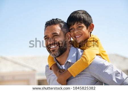 Happy middle eastern child enjoying ride on father back outdoor. Smiling dad giving piggyback ride to son on street while looking away with copy space. Indian cheerful man carrying on shoulder kid.