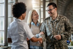 Happy military man shaking hands with female doctor while being with his wife at medical counselling.