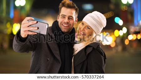 Happy millenial couple having fun taking selfies together at night in the city